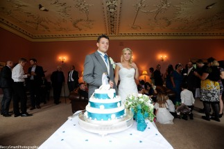 bride and groom by their wedding cake